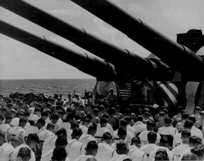 The crew of the USS SOUTH DAKOTA stands with bowed heads, while Chaplain N. D. Lindner reads the benediction held in honor of fellow shipmates killed in the air action off Guam on June 19, 1944. Source: National Archives.