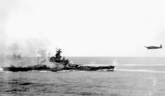 "The U.S. Navy battleship USS South Dakota (BB-57) firing her anti-aircraft guns at attacking Japanese planes during the Battle of Santa Cruz, 26 October 1942. A Japanese Type 97 Nakajima B5N2 torpedo plane (""Kate"") is visible at right, apparently leaving the area after having dropped its torpedo. Source: Official U.S. Navy photograph 80-G-30054 from the U.S. Navy Naval History and Heritage Command."